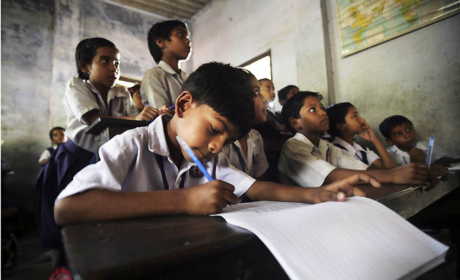Indian students take lessons from their teacher inside a classroom at a school in Calcutta, India, Thursday, April 1, 2010. A law making primary education compulsory in India came into effect Thursday, opening the door for millions of impoverished children who have never made it to school because their parents could not afford the fees or because they were forced to work instead. (AP Photo/Sucheta Das)